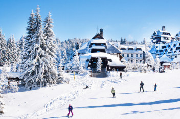 Panorama of ski resort Kopaonik, Serbia, ski slope, chalet houses covered with snow, people skiing